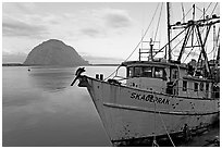 Baat with rusted hull and Morro Rock. Morro Bay, USA ( black and white)