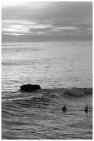 Surfers and rock at sunset. Santa Cruz, California, USA ( black and white)