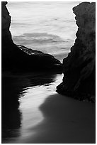 Reflection on wet sand through rock opening, Natural Bridges State Park, dusk. Santa Cruz, California, USA ( black and white)