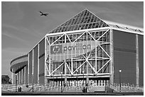 HP Pavilion with person and plane, late afternoon. San Jose, California, USA (black and white)