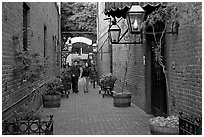 Couple walking in an alley of brick walls, San Pedro Square. San Jose, California, USA (black and white)