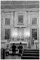 Prayer at altar in Mission Chapel. Los Angeles, California, USA (black and white)