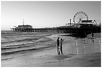 Couple on beach, with pier in the background, sunset. Santa Monica, Los Angeles, California, USA (black and white)