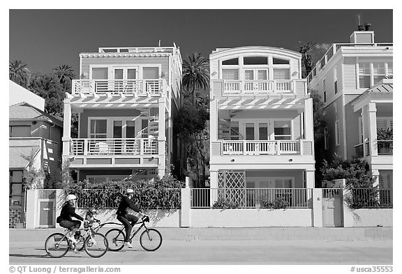 Family cycling in front of colorful beach houses. Santa Monica, Los Angeles, California, USA (black and white)