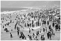 Crowds of beachgoers in water. Santa Monica, Los Angeles, California, USA (black and white)