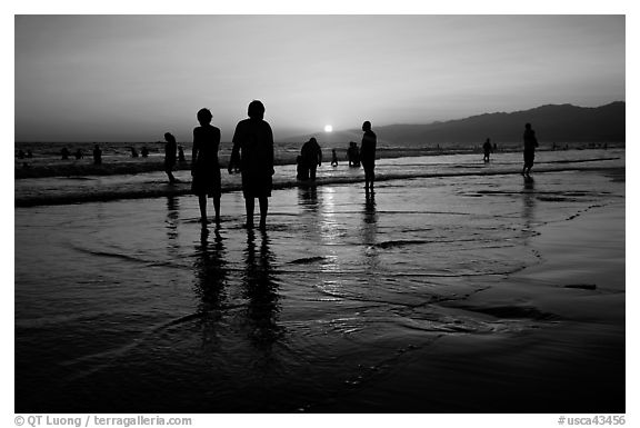 People and reflections on beach at sunset, Santa Monica Beach. Santa Monica, Los Angeles, California, USA (black and white)