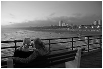 Two women sitting on bench at sunset , Santa Monica Pier. Santa Monica, Los Angeles, California, USA (black and white)