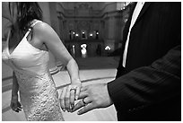 Newly wed couple holds hands, showing ring, City Hall. San Francisco, California, USA (black and white)
