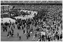 Audience and graduates mingling in stadium after commencement. Stanford University, California, USA (black and white)