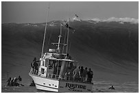 Judging boat with huge wave and surfer at crest. Half Moon Bay, California, USA (black and white)