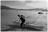 Man boards sea kayak, Carmel Bay. Carmel-by-the-Sea, California, USA ( black and white)