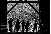 Silhouettes of dancers with sticks inside covered bridge, Felton. California, USA (black and white)