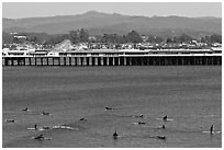 Surfers and municipal wharf. Santa Cruz, California, USA ( black and white)
