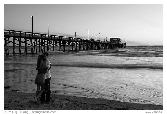 Couple embracing in front of Newport Pier. Newport Beach, Orange County, California, USA (black and white)