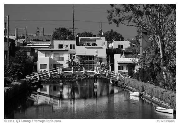 Rower under bridge next to colorful houses. Venice, Los Angeles, California, USA (black and white)