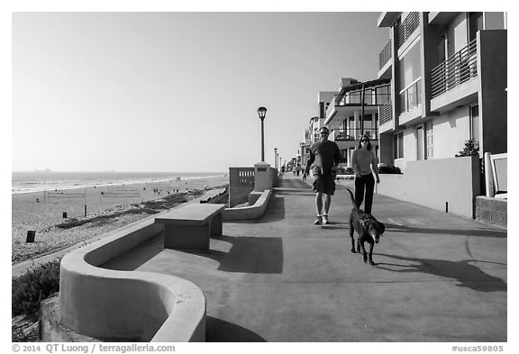 Couple walking dog on beachfront promenade, Manhattan Beach. Los Angeles, California, USA (black and white)