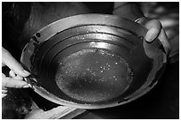 Hands holding pan with bits of gold, El Dorado County. California, USA ( black and white)