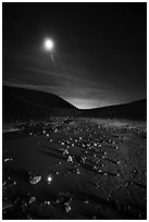 Puddle and cracked mud in Amboy Crater at night. Mojave Trails National Monument, California, USA ( black and white)