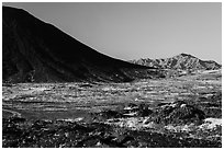 Lava field, Amboy Crater slope and mountains. Mojave Trails National Monument, California, USA ( black and white)