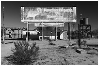 Old billboard and abandonned gas station. Mojave Trails National Monument, California, USA ( black and white)