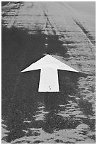 Painted arrow, asphalt, and sand, Cape Cod National Seashore. Cape Cod, Massachussets, USA ( black and white)