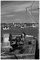 Man preparing to lift box from deck. Corea, Maine, USA ( black and white)