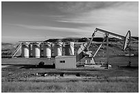 Pumping unit and tanks, oil well. North Dakota, USA (black and white)