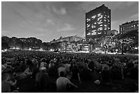 Crowd sitting on lawn during evening outdoor concert, Central Park. NYC, New York, USA ( black and white)