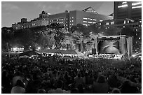 Outdoor musical performance at night with QTL photo as screen backdrop, Central Park. NYC, New York, USA ( black and white)