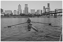 Woman rowing on racing shell and city skyline at sunrise. Portland, Oregon, USA ( black and white)