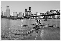 Rowers on double-oar shell lauching from deck in front of skyline. Portland, Oregon, USA ( black and white)