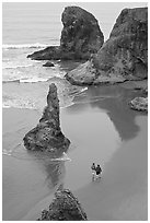 Women walking on beach among rock needles. Bandon, Oregon, USA ( black and white)