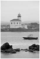 Small boat and Coquille River lighthouse. Bandon, Oregon, USA ( black and white)