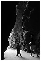 Father and son walking towards the light in sea cave. Bandon, Oregon, USA ( black and white)