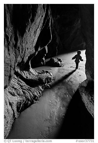Infant walking out of sea cave. Bandon, Oregon, USA