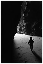 Infant walking towards the light in sea cave. Bandon, Oregon, USA ( black and white)