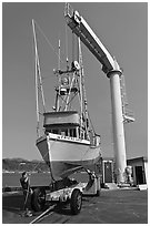 Fishing boat lifted from water by huge hoist, Port Orford. Oregon, USA ( black and white)