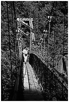 Woman hiking on suspension bridge, Lava Canyon. Mount St Helens National Volcanic Monument, Washington ( black and white)