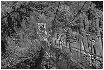 Hikers cross suspension bridge over Lava Canyon. Mount St Helens National Volcanic Monument, Washington ( black and white)