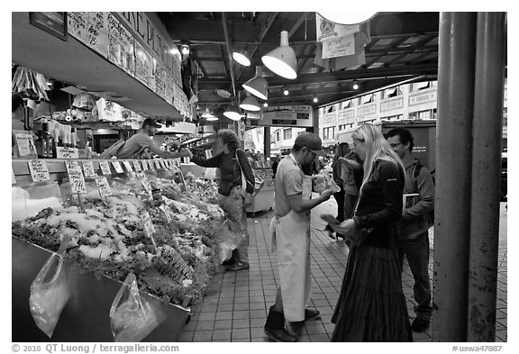 Countermen offer fish samples, Pike Place Market. Seattle, Washington (black and white)