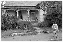 Woman walking dog in front of a crooked house. Selma, Alabama, USA (black and white)