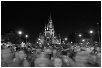 Crowds on Main Street with castle in the back at night. Orlando, Florida, USA ( black and white)
