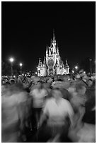 Crowds walking away from Cinderella Castle at night. Orlando, Florida, USA ( black and white)