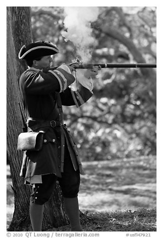 Man in period costume fires smooth bore musket, Fort Matanzas National Monument. St Augustine, Florida, USA (black and white)