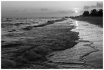 Beach with people in the distance at sunset, Sanibel Island. Florida, USA (black and white)