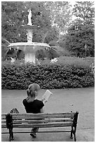 Woman reading a book in front of Forsyth Park Fountain. Savannah, Georgia, USA ( black and white)