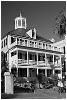 Couple walking in front of antebellum house. Charleston, South Carolina, USA (black and white)