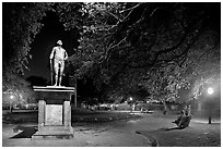 Park with statue and couples sitting on public benches at night. Charleston, South Carolina, USA (black and white)