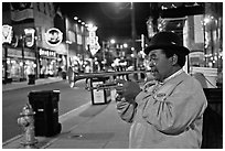 African-American man playing trumpet on Beale Street by night. Memphis, Tennessee, USA (black and white)