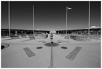 Woman straddling the territory of four states. Four Corners Monument, Arizona, USA ( black and white)